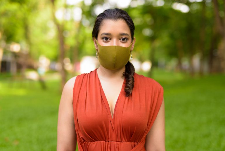 Portrait of young Indian woman with mask for protection from corona virus covid-19 outbreak at the park outdoors